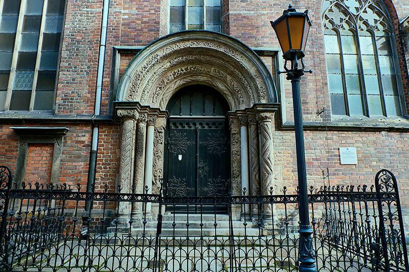Latarnia z oprawą 01 VERA na tle drzwi do Kościoła
