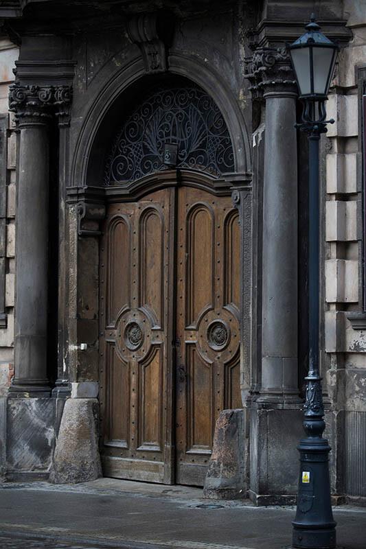 Latarnia z dekoracją wykonaną z aluminium na tle drzwi